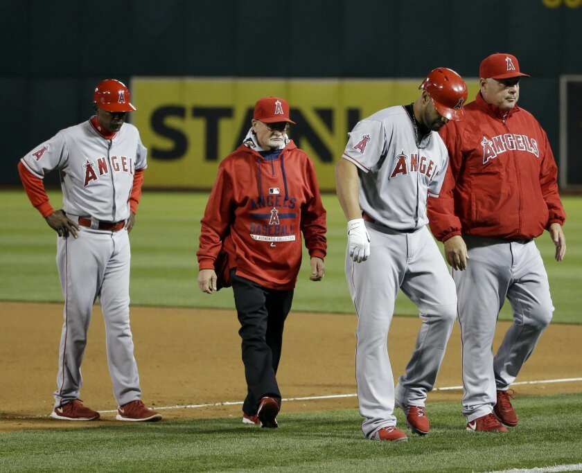 Los Angeles Angels' Albert Pujols, second from right, leaves the game with an injury alongside manager Mike Scioscia, right, during the sixth inning of a baseball game against the Oakland Athletics Wednesday, April 29, 2015, in Oakland, Calif. (AP Photo/Marcio Jose Sanchez)