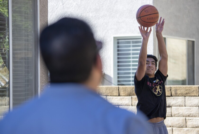 Bishop Alemany High guard Nico Ponce, right, works out on his backyard court with father Manuel at their home in Castaic.