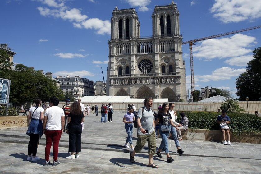 People walk on the forecourt of Notre Dame's Cathedral, in Paris, Sunday, May 31, 2020. Notre Dame Cathedral's forecourt is being opened up to the public for the first time since the devastating fire of April 15 last year. (AP Photo/Thibault Camus)