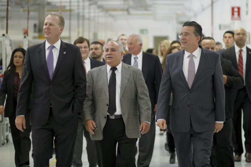 San Diego Mayor Kevin Faulconer, left, tours Plantronics facility in Tijuana together with Allejandro Bustamante, the company's senior vice president of worldwide operations, center and Tijuana Mayor Jorge Astiazaran, right.