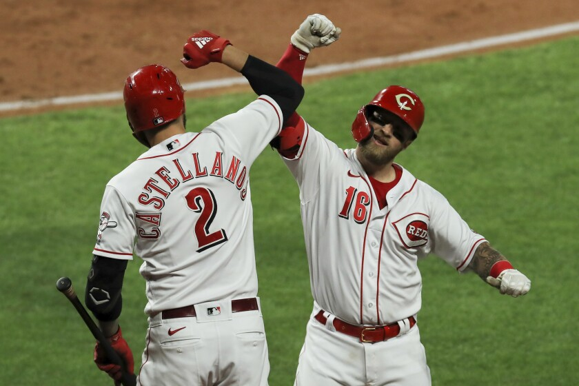 Cincinnati Reds' Nick Castellanos, left, and Tucker Barnhart celebrates Barnhart's solo home run during the third inning of the team's baseball game against the Chicago White Sox in Cincinnati, Friday, Sept. 18, 2020. (AP Photo/Aaron Doster)