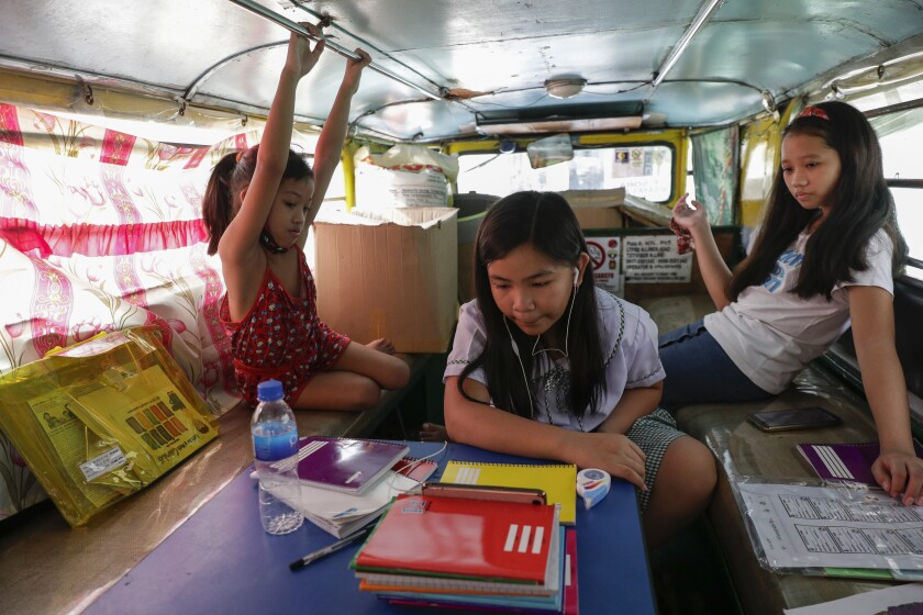 Grade school student Bhea Joy Roxas, center, uses a smart phone as she joins online classes while her friends observe inside a passenger jeepney at the Tandang Sora jeepney terminal in Quezon city, Philippines on Monday, Oct. 5, 2020. Students in the Philippines began classes at home Monday after the coronavirus pandemic forced remote-learning onto an educational system already struggling to fun schools. The two students missed the flag raising ceremony due to poor internet connection. (AP Photo/Aaron Favila)