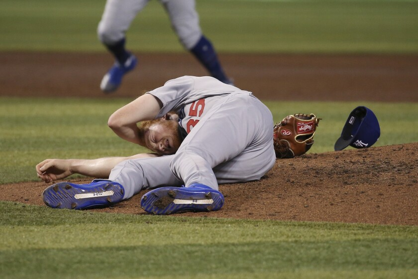 Dodgers pitcher Dustin May rolls on the ground after being hit in the head by a line drive off the bat of the Diamondbacks' Jake Lamb during the fourth inning.