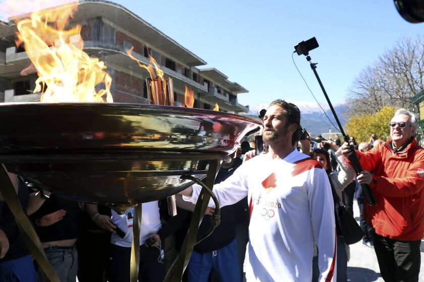 """US actor Gerard Butler lights an altar as a torchbearer during the Olympic torch relay of the 2020 Tokyo Olympic Games in the southern Greek town of Sparta, Friday, March 13, 2020. Greece's Olympic committee says it is suspending the rest of its torch relay for the Olympic flame due to the """"unexpectedly large crowd"""" that gathered to watch despite repeated requests for the public to stay away to prevent the spread of the new coronavirus. (AP Photo)"""
