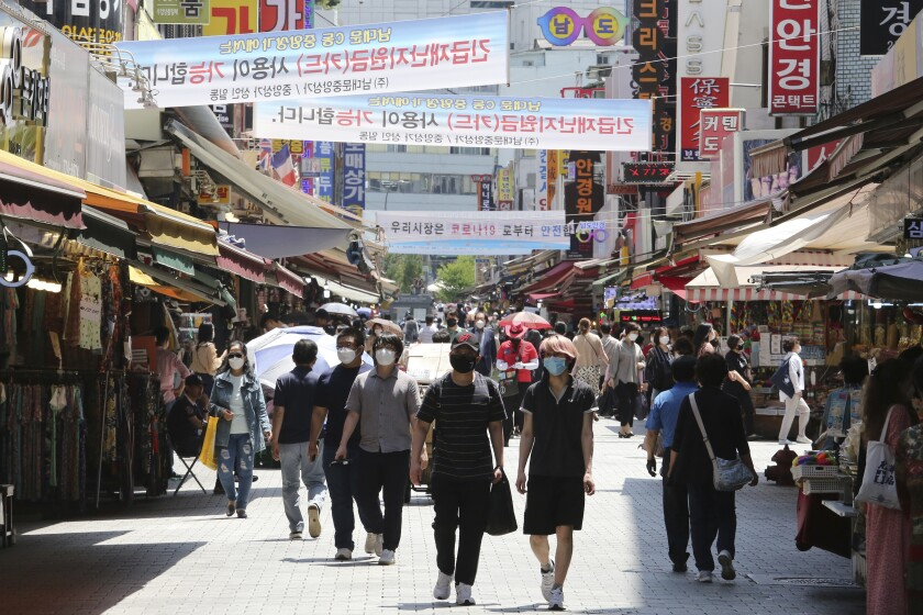 FILE - In this June 11, 2020, file photo, people walk on a shopping district in Seoul, South Korea. South Korea has reported nearly 50 cases of COVID-19 as the virus continues to spread in the densely populated capital area where half of the country's 51 million people live, according to figures released by the Korea Centers for Disease Control and Prevention on Friday, June 19, 2020. (AP Photo/Ahn Young-joon, File)