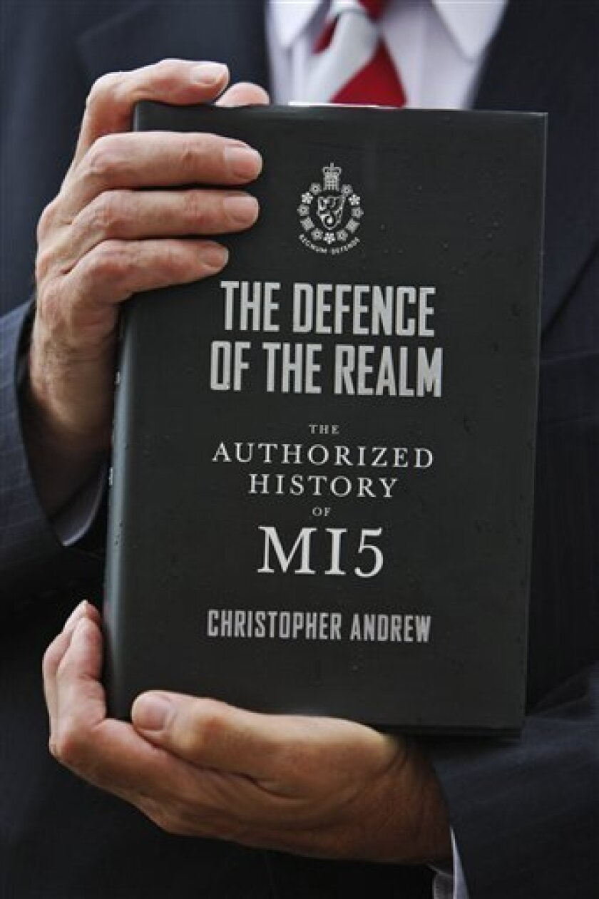 Christopher Andrew, author of 'The Defence of the Realm, The Authorized History of MI5' poses for the photographers holding a copy of his book, following a news conference in central London, Monday Oct. 5, 2009. To mark the centenary of its foundation, the British Security Service, MI5, has opened its archives to an independent historian, the first time any of the world's leading intelligence or security services has taken such a step. (AP Photo/Lefteris Pitarakis)