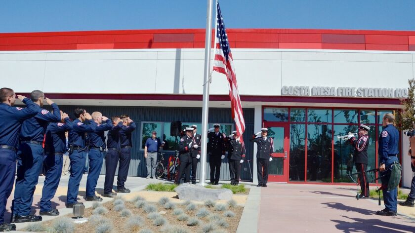 The Costa Mesa Fire Department Honor Guard raises the flag in front of the new building during the S