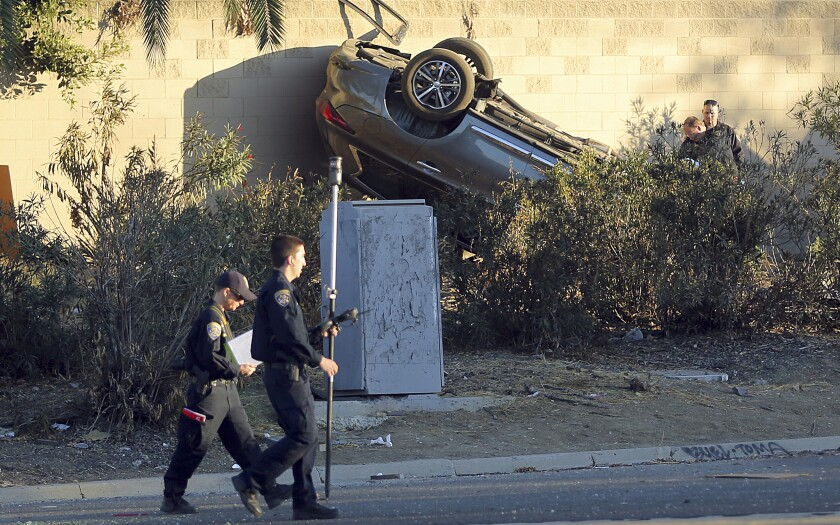 California Highway Patrol investigators view the scene of a pursuit that ended in a crash on the Hollywood Freeway near downtown Los Angeles Friday, Nov. 1, 2019. Three people in the car died at the scene; a fourth was in a hospital in critical condition. (AP Photo/Reed Saxon)