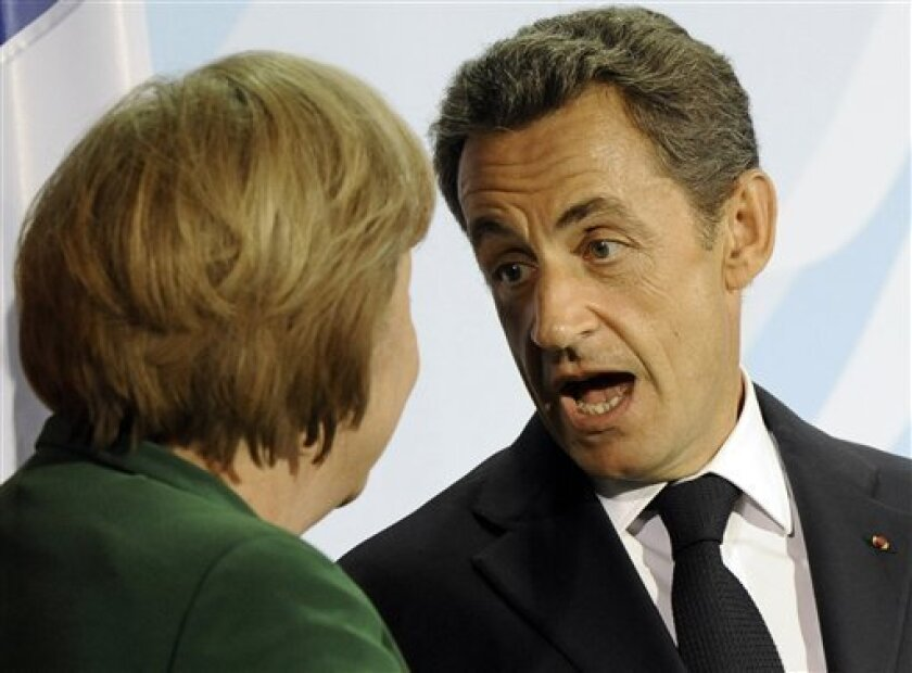 French President Nicolas Sarkozy, right, reacts to German Chancellor Angela Merkel after a meeting on the financial crisis in Berlin, Germany, Sunday, Oct. 9, 2011. The two leaders of the eurozone's two biggest economies, say they have reached agreement on strengthening Europe's shaky banking sector. (AP Photo/Martin Meissner)