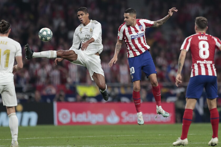 Real Madrid's Raphael Varane jumps to kick the ball before Real Madrid's Marco Asensio, center right, during the Spanish La Liga soccer match between Atletico Madrid and Real Madrid at the Wanda Metropolitano stadium in Madrid, Saturday, Sept. 28, 2019. (AP Photo/Bernat Armangue)