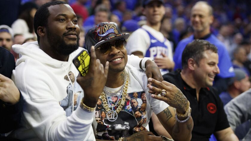 Former 76ers' Allen Iverson, right, poses with rapper Meek Mill, left, during the first half of Game
