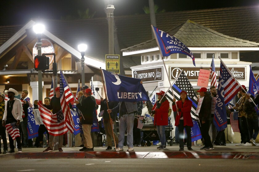 Protesters gather in front of the Huntington Beach Pier Saturday to protest a nearly statewide nighttime curfew.