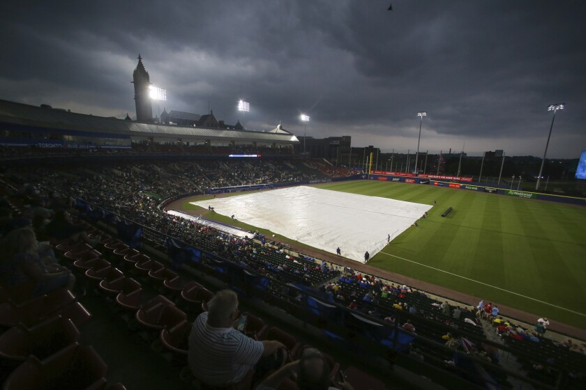Fans watch as the grounds crew covers the infield with a tarp before the baseball game between the Toronto Blue Jays and Boston Red Sox on Tuesday, July 20, 2021, in Buffalo, N.Y. The game was postponed due to a thunderstorm in the area. (AP Photo/Joshua Bessex)