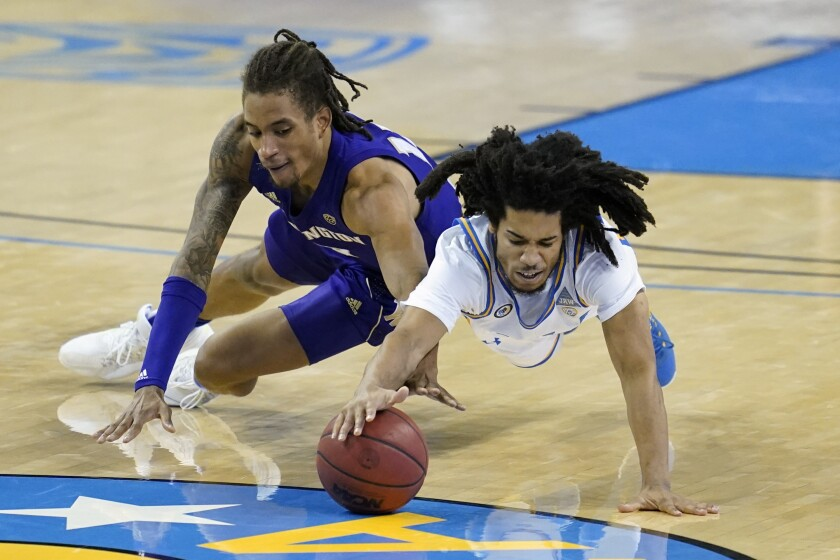 UCLA guard Tyger Campbell and Washington forward Hameir Wright dive for a loose ball.