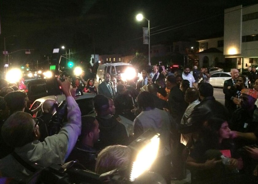 Black Lives Matter protesters swarm L.A. Mayor Eric Garcetti's car after a community meeting was cut short Monday night at Holman United Methodist Church in South Los Angeles.