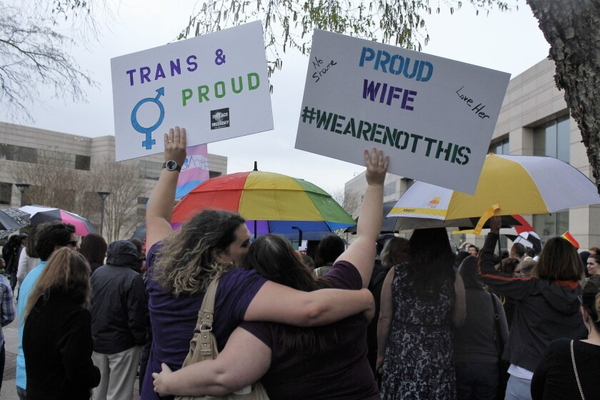 During a rally in Charlotte, N.C., in March, two protesters hold signs against the passage of legislation in the state that limits bathroom options for transgender people.