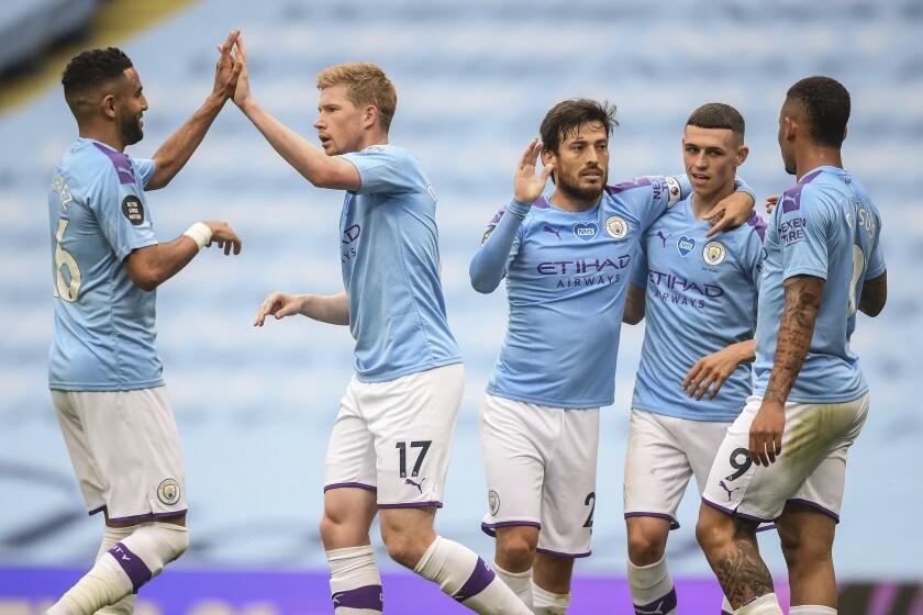 Jugadores del Manchester City celebran su segundo gol en un partido de la Premier League contra el Newcastle, en el estadio Etihad de Manchester, Inglaterra, el miércoles 8 de julio de 2020. (Michael Regan/Pool via AP)