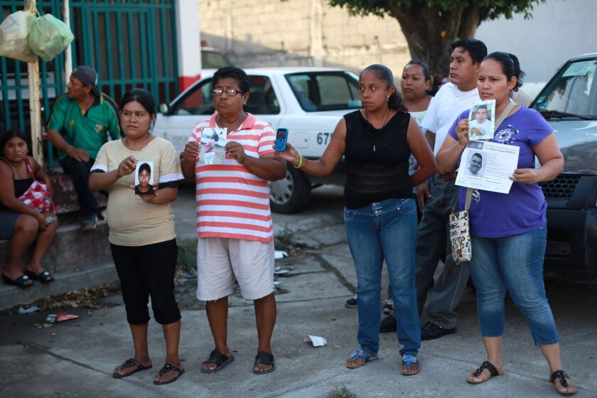 People hold portraits of their missing loved ones in front of the morgue of Cosamaloapan, with the hope of finding and identifying the bodies of their missing, from a mass grave which has been recently discovered, in Veracruz , Mexico, Wednesday, June 18, 2014. At least 28 bodies have been recovere