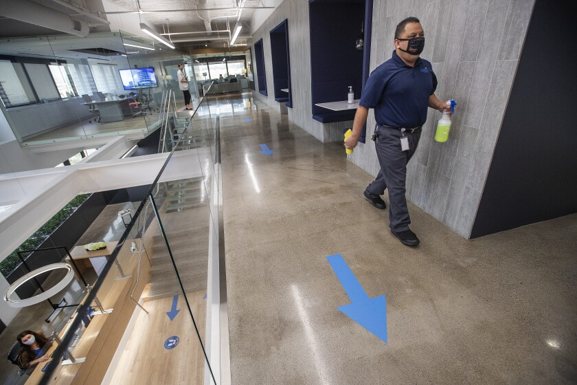 A man walks with disinfectant while cleaning a common area at Hudson Pacific Properties in Los Angeles.