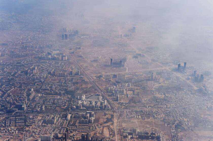 Smog envelops buildings on the outskirts of India's capital city of New Delhi on Nov. 25, 2014.