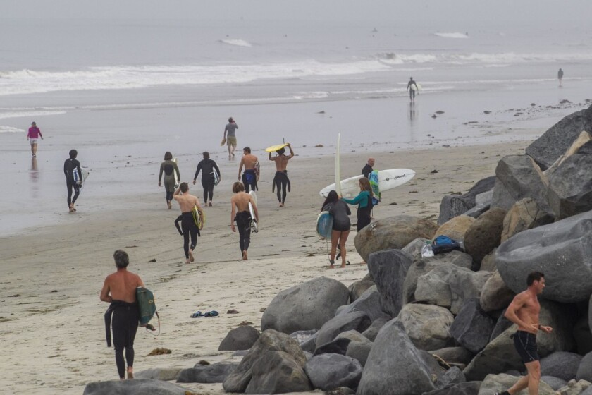 Early Monday morning on April 27, 2020 the City of Encinitas reopened its beaches in a limited manner. Surfers walked up and down the beach at low tide to get to their favorite surf spots. The city is trying to channel all beach users through the Moonlight Beach Park.