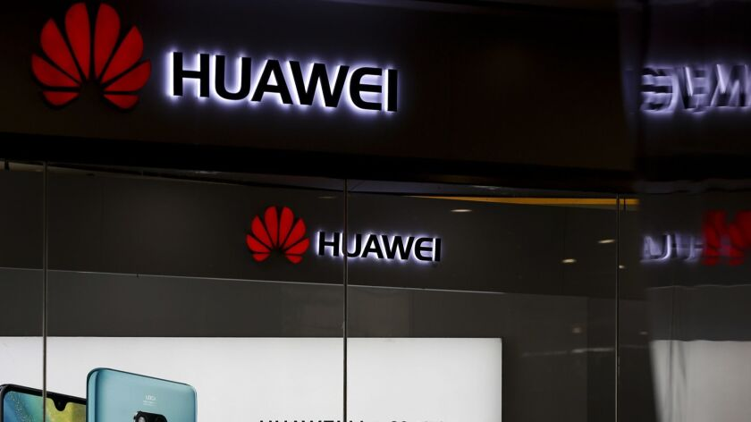 A man walks past a Huawei retail store in Beijing, Wednesday, May 29, 2019. Chinese tech giant Huawe