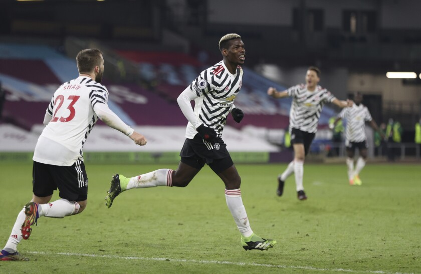 Manchester United's Paul Pogba, center, runs to celebrate after scoring during the English Premier League soccer match between Burnley and Manchester United in Burnley, England, Tuesday, Jan. 12, 2021. Manchester won the match 1-0.(Clive Brunskill/Pool via AP)