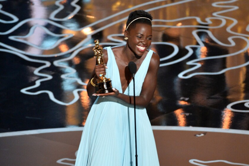 """Actress Lupita Nyong'o accepts the Oscar for supporting actress for her role in """"12 Years a Slave."""""""