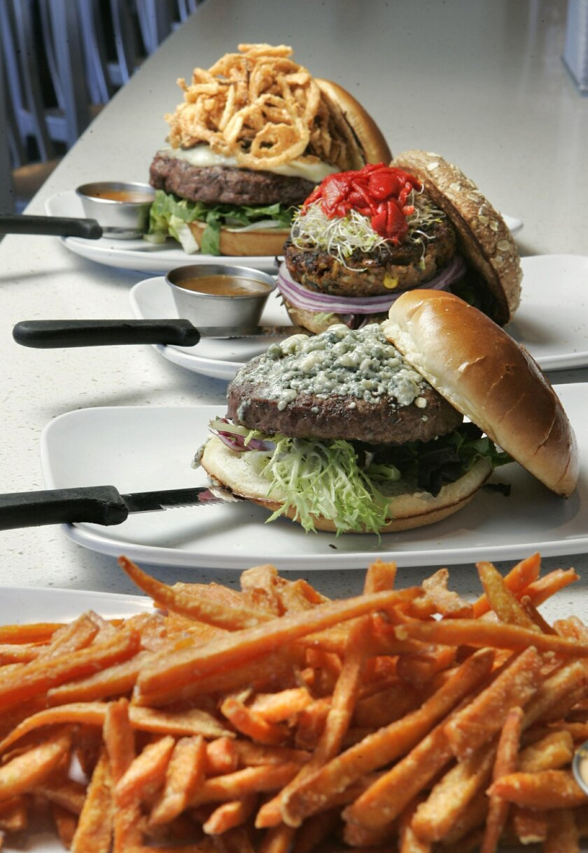 """Three of The Counter's """"Signature Burgers"""" with Sweet Potato Fries (bottom to top): Mixed Greens, Unique Veggie and the 2/3-pound Counter Burger."""