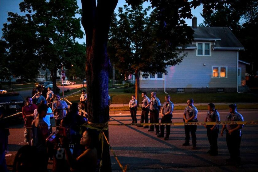 Police form a line in the street as a crowd grew Saturday night in response to an earlier officer-involved shooting.