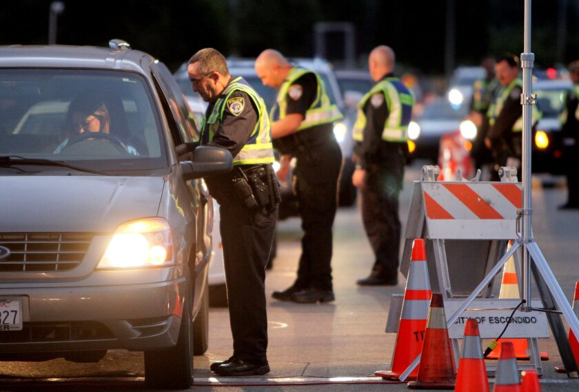 Escondido police officers check motorists entering a DUI and driver's license checkpoint at dusk at eastbound El Norte Parkway and Ash Street on Oct. 23. / CHARLIE NEUMAN • U-T