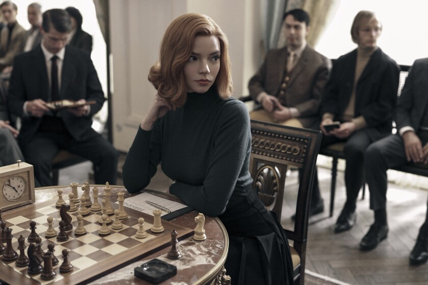"Anya Taylor-Joy sitting in front of a chess board in the Netflix drama ""The Queen's Gambit."""