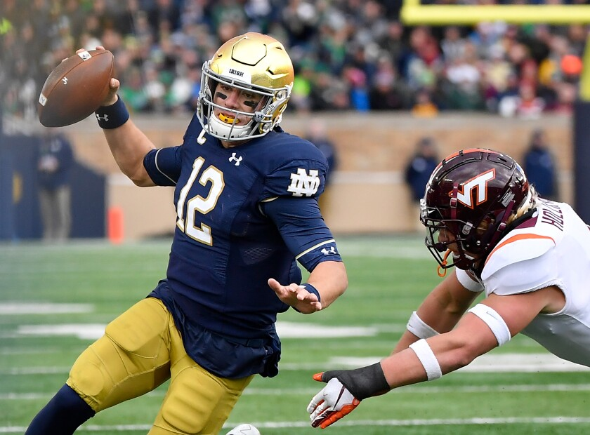 Notre Dame quarterback Ian Book scrambles against Virginia Tech on Saturday in South Bend, Ind.