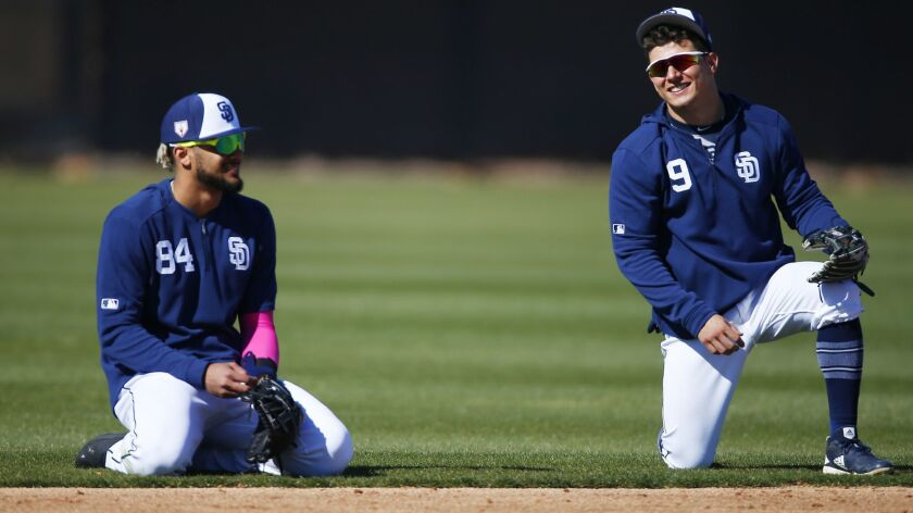 Padres infielders Fernando Tatis Jr. (left) and Luis Urias wait for drills during a spring training practice.