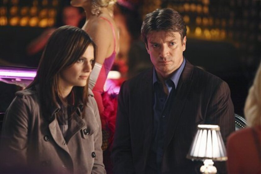 """In this undated publicity image released by ABC, Stana Katic, left, and Nathan Fillion are shown in a scene from """"Castle."""" (AP Photo/ABC, Adam Larkey)"""