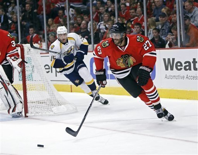 Chicago Blackhawks defenseman Johnny Oduya heads upice with the puck while being chased by Nashville Predators' Craig Smith during the first period in an NHL hockey game in Chicago, Sunday, April 7, 2013. (AP Photo/Charles Cherney)