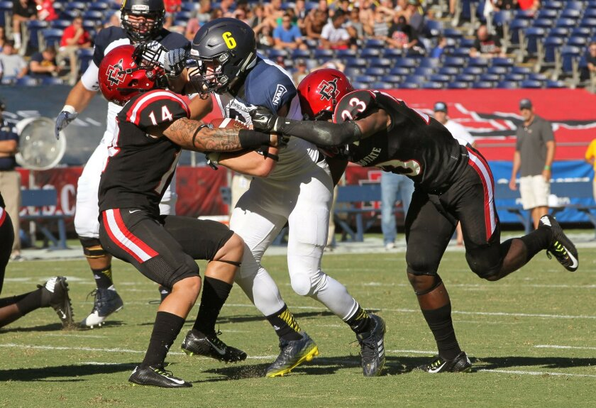 NAU running back Casey Jahn gets tackled by Aztecs' Trey Lomax, at left, and Damontae Kazee, at right.