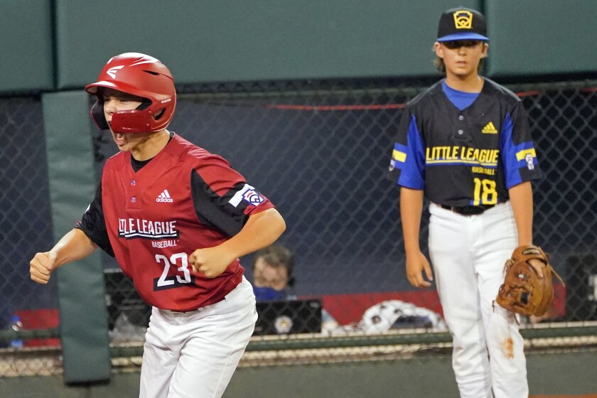 Hamilton, Ohio's JJ Vogel celebrates scoring on a  triple by Chance Retherford as Torrance pitcher Dominic Golia watches.