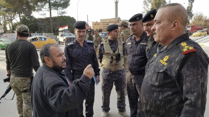Residents greet Mosul police Chief Wathaq Hamdani as he tours a neighborhood on the city's east side Wednesday.