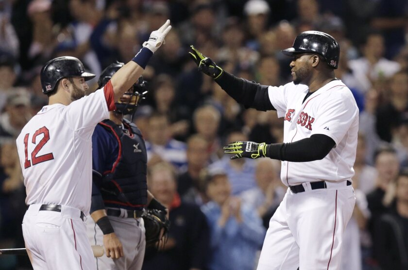Boston Red Sox designated hitter David Ortiz, right, is congratulated by teammate Nike Napoli (12) after hitting a two-run home run off Cleveland Indians starting pitcher Josh Tomlin during the fifth inning of a baseball game at Fenway Park in Boston, Thursday, June 12, 2014. Indians catcher Yan Gomes, center, looks on. (AP Photo/Charles Krupa)