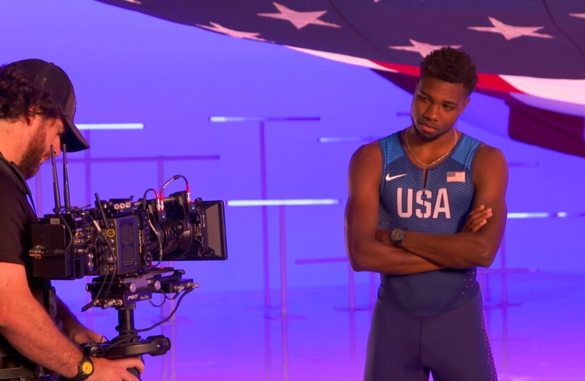 """Noah Lyles on a """"flag"""" soundstage. NBCUniversal recently summoned 110 U.S. athletes to a West Hollywood studio, shepherding them through soundstages, photo shoots and recording booths, taping interviews for use during the Games and, just as important, gathering raw material for ads and promos right now."""