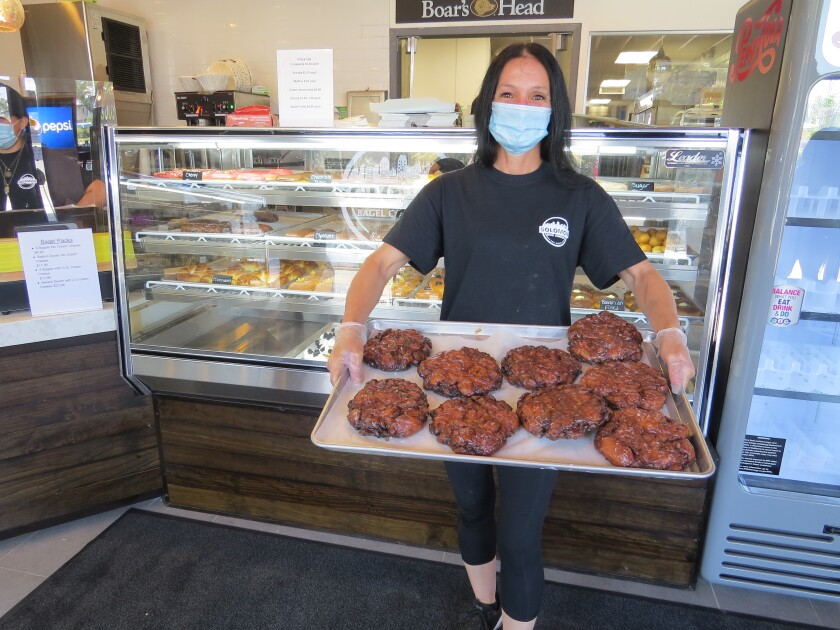 Doughnut baker Tammy Strange holds a tray of her popular apple fritters at Solomon Bagels & Donuts in North Park.