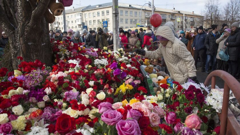 People leave flowers on March 26, 2018, in tribute to the victims of a fire at a multi-story shopping center in the Siberian city of Kemerovo, Russia.