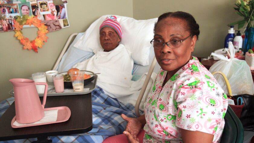 Ena McIntyre, who is a licensed vocational nurse at Sharp Grossmont Hospital, visits her mother, Gwennie Bannis, at the La Mesa Healthcare Center in La Mesa. McIntyre visits her 97-year-old mother every day, bringing clean clothes and homemade soup.