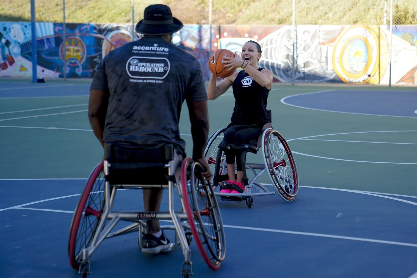 Army veteran Anthony Pone, left, practices with teammate Megan Blunk on the basketball court at Chicano Park in San Diego on Oct. 8. Pone and Blunk play for the Wolfpack, a wheelchair basketball team made up of disabled active-duty military and veterans.