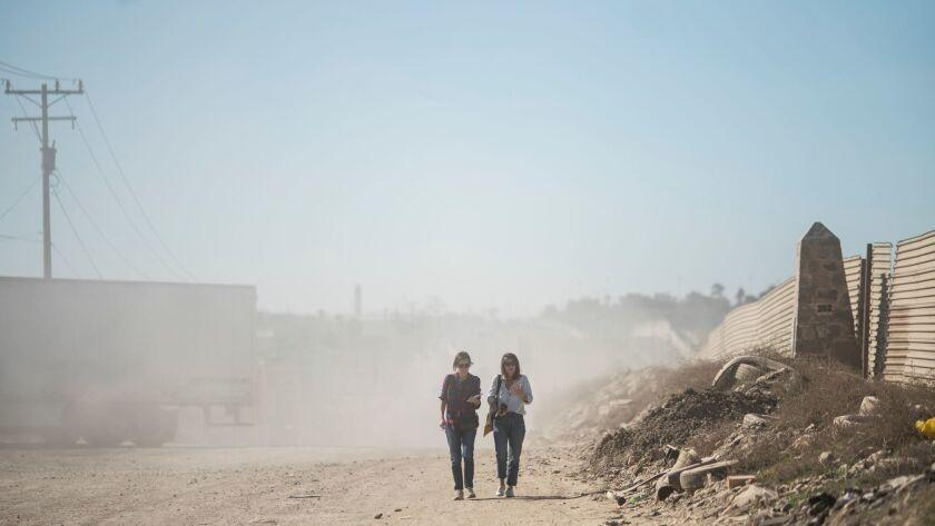 TIJUANA, B.C., MEX - FEBRUARY 01: Corine Lensnes and Shanna Yates walk along a dusty road with a tou