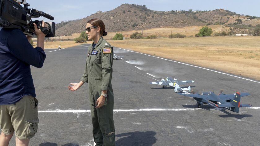Navy pilot Lt. Leslie Garcia explains the working of an aircraft carrier's flight deck using model airplanes while being interviewed by a UK documentary production company that is doing a project having to do with angled flight decks found on aircraft carriers.