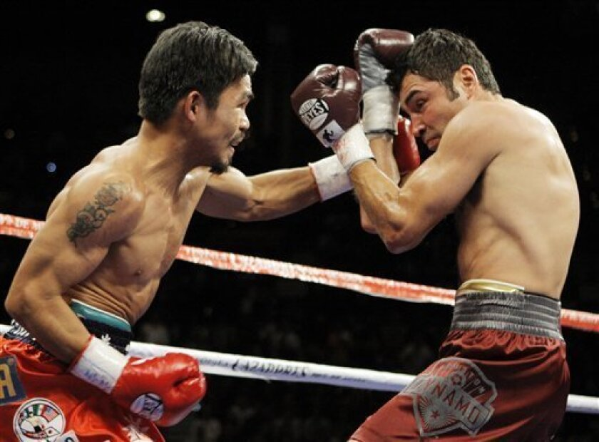 WBC lightweight champion Manny Pacquiao throws a left to the head of Oscar De La Hoya during the first round of their welterweight boxing match in Las Vegas, Saturday, Dec. 6, 2008. (AP Photo/Jae C. Hong)