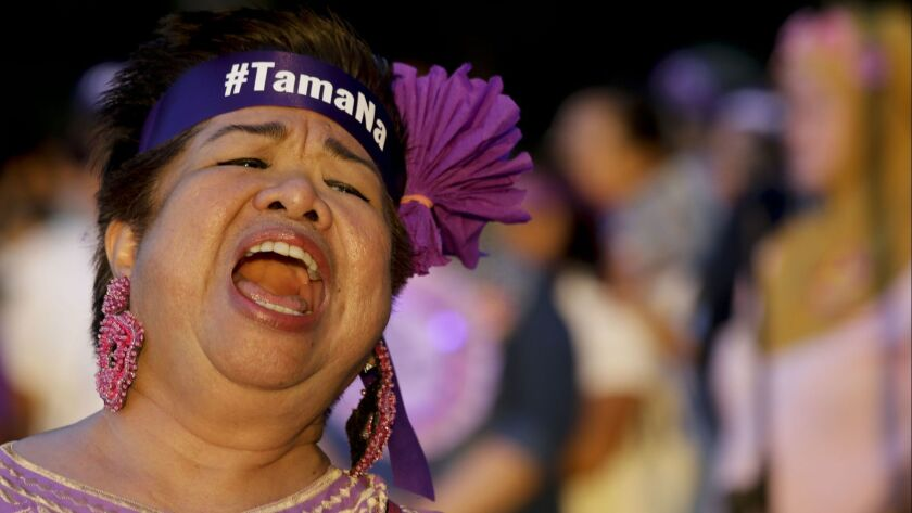 """A woman activist wearing a headband with a sign that reads """"enough"""" shouts slogans as their group ma"""