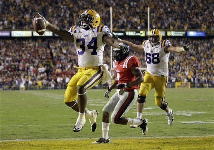 """FILE - In this Nov. 20, 2010, file photo, LSU running back Stevan Ridley (34) celebrates as he scores a touchdown during an NCAA college football game against Mississippi in Baton Rouge, La. A person familiar with Ridley's eligibility status says the Tigers' leading rusher has been cleared to play against Texas A&M in the Cotton Bowl on Friday, Jan. 7. Ridley's eligibility had been in doubt since head coach Les Miles said on Dec. 22 that the running back could miss the game because of an unspecified """"one-time"""" academic violation. (AP Photo/Patrick Semansky, File)"""